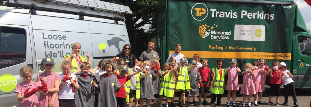A class of children and their teachers give a thumbs up to the camera. They are standing in front of a Travis Perkins lorry and a white van.