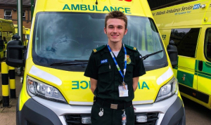 Daniel smiles at the camera. He is wearing his paramedic uniform and stands in front of a yellow ambulance.