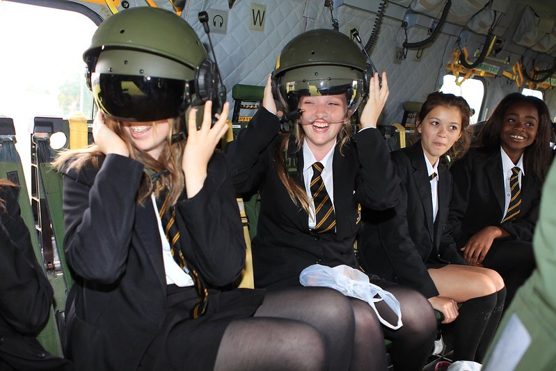 Four girls smile while sitting in an aircraft, and two of them try on helmets.
