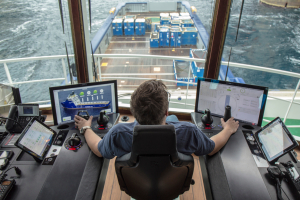 Person sits in a chair and holds controls. They are looking out onto the front of a ship. Either side of them is a screen displaying graphics and a diagram of a ship.