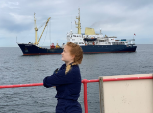 Miriam stands by a red rail and looks out to see. A ship is in the background.